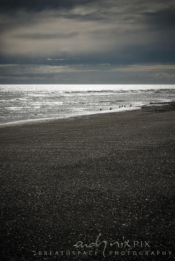 Dark pebble beach with sun bleaching water, clouds in sky