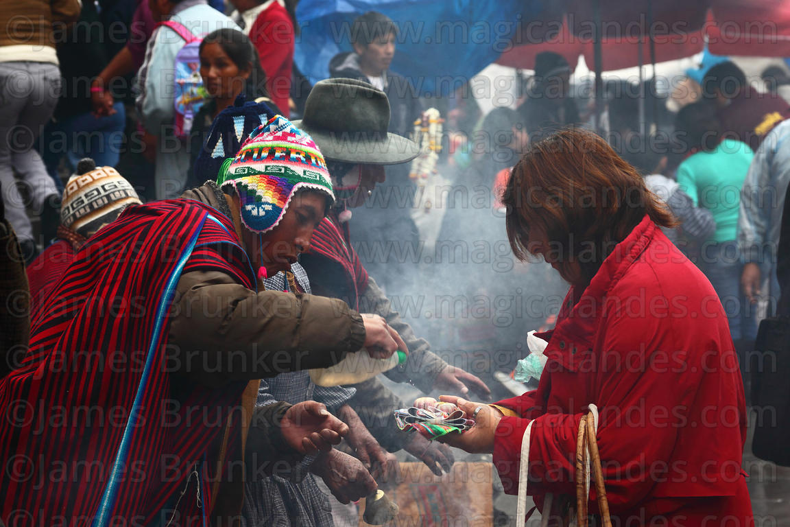 A yatiri or shaman blesses miniatures with alcohol, Alasitas festival, La Paz, Bolivia