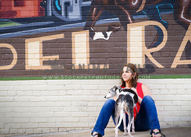 whippet dog and owner in front ow mural on brick wall