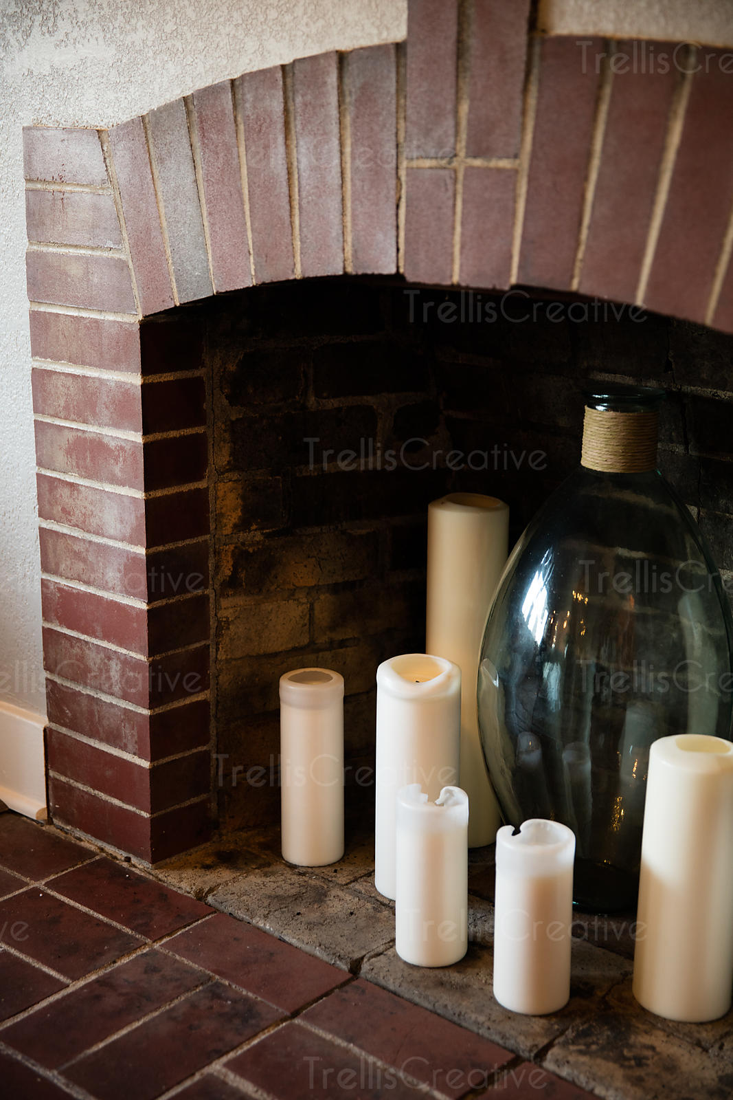 Candles and glassware inside a brick fireplace