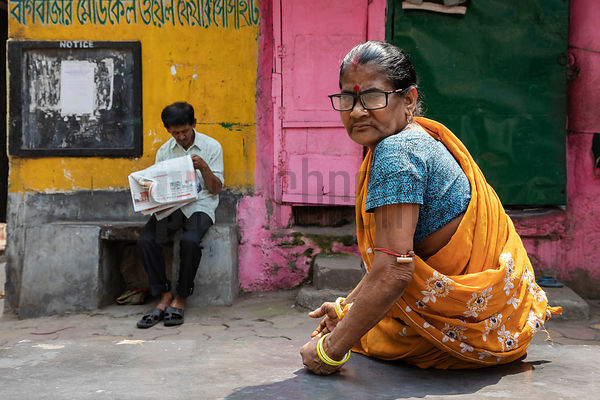 Woman in a Yellow Sari Sitting on a Concrete Bench