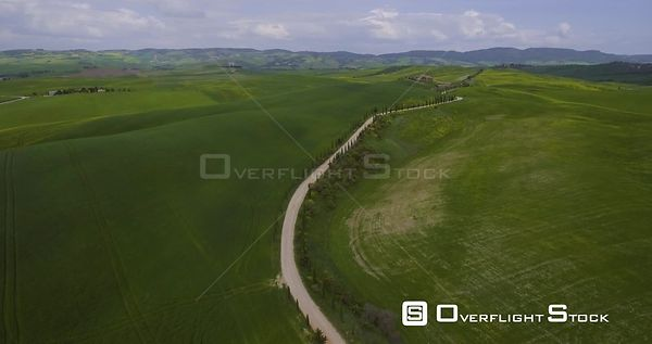 Aerial, a road with cypresses in Tuscany fields and hills
