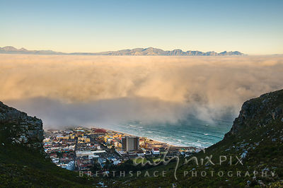 View above fog over False Bay, small patch of beach, sea and village visable  at the foot of the mountain below the cloud, mo...