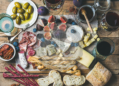 Wine and snack set with various wines in glasses, meat variety, ciabatta, sun-dried tomatoes, honey, green olives, figs, nuts...
