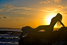 Mermaid on ironshore at sunset, Cozumel, Mexico