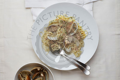 Linguine with Clams in a bowl with a white Linen surface.