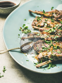 Grilled lamb ribs with green parsley and sauce in plate