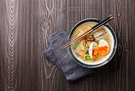 Chinese noodles with egg, tofu and enoki in bowl on gray wooden background