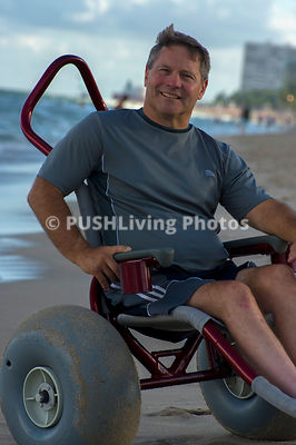 Man enjoying the ocean in a beach wheelchair