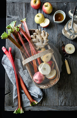 Apples and rhubarb in a basket on a wooden background
