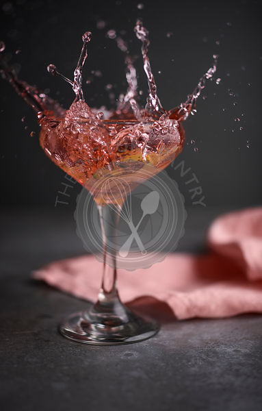 A rich pink cocktail splash on metal surface with pink linen