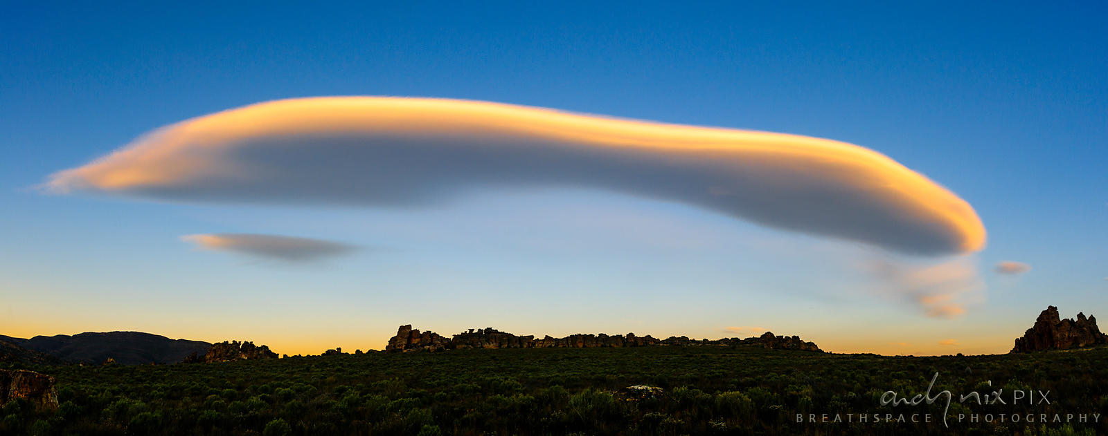 soft long cloud over rocky fynbos landscape.