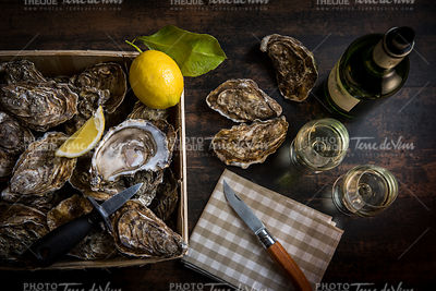 Raw oysters basket with lemon on wood board and bottle of wine and glass