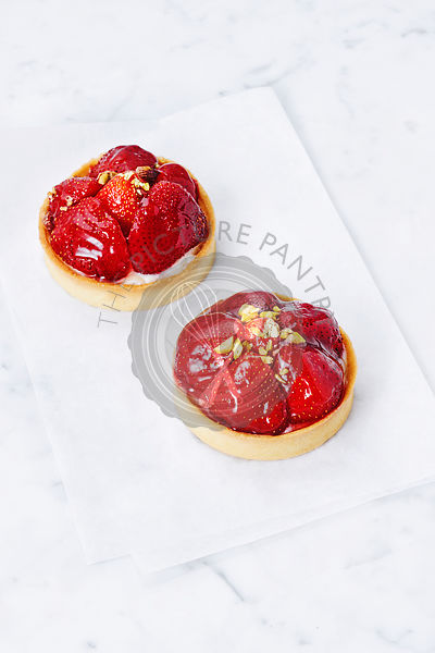 Two glazed strawberry tarts, elevated view