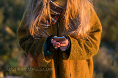 Young woman holding cell phone outdoors