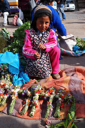 Girl selling crosses made out of local plants for Easter in market , Cusco , Peru