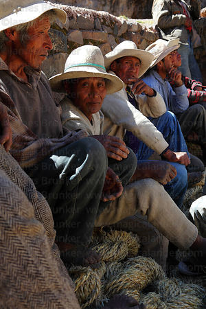 Tired men take a break from hauling new foundation ropes across the canyon , Q'eswachaka , Canas province , Peru