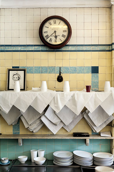 UK - London - An antique clock, plates and paper bags on the wall of  F Cooke's Pie and Mash shop