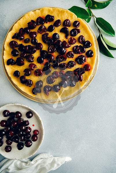 Pie dough topped with cherries, pitted cherries on a white plate and green leaves on grey background photographed from top view.