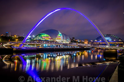 Newcastle's Millenium Bridge lit with blue light with the Sage Gateshead venue reflecting brightly in the River Tyne.