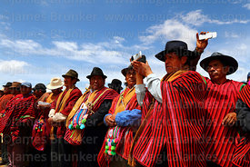 Local community leaders using smartphone and video recorder to film dances at a festival, Umala, Bolivia