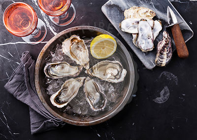 Opened Oysters on metal plate and rose wine on dark marble background