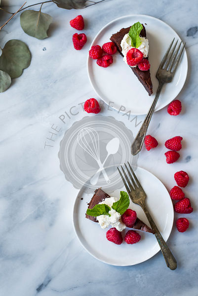 Dark chocolate cake with fresh whipped cream, fresh berries on white plates.