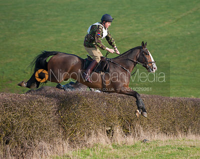 Riders jump a big hedge early on the course