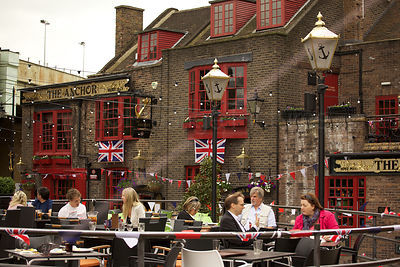 People Sitting and Drinking by Quaint Pub on The RIver Thames