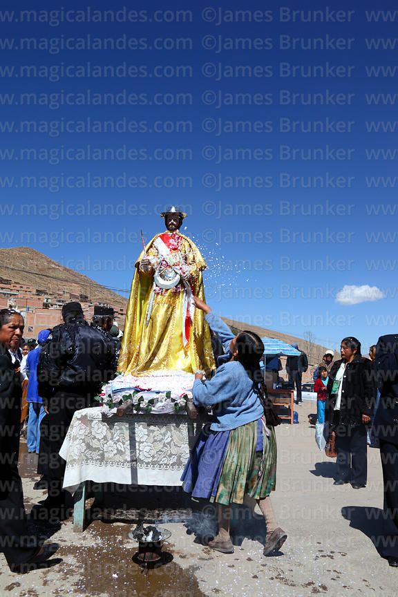 Indigenous lady throws confetti over San Bartolome during procession at start of Chutillos festival, Potosí, Bolivia