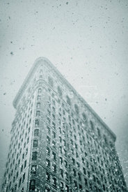An atmospheric image of a the Flatiron building, in New York City, on a wintery day.