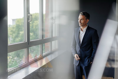 Businessman in office looking out of window