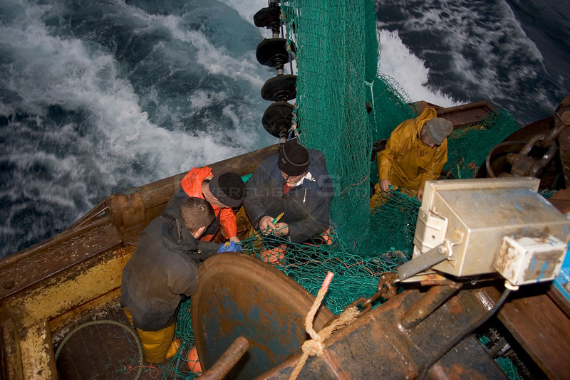 Fishermen repairing torn nets after snagging a seabed obstruction in the North Sea, August 2006.
