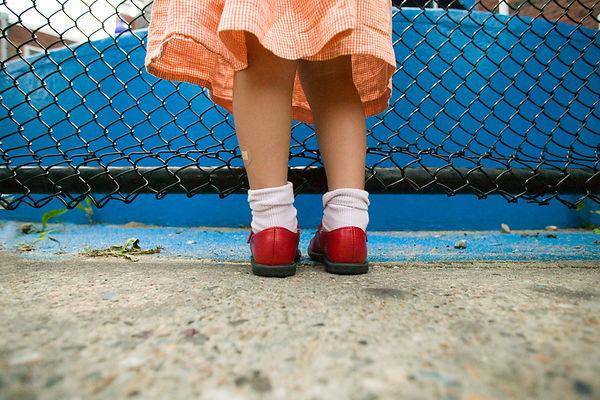 child's feet with red shoes