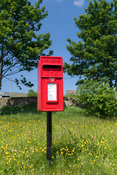 Red post box in a rural situation, North Yorkshire, UK.