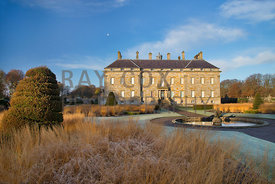 Frosted grasses, yew topiary spirals, circular pond and house