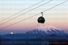 Yellow Line cable car gondola above Mt Illimani and full moon just rising, La Paz, Bolivia