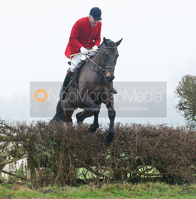 Andrew Osborne jumping a hedge from the meet - The Cottesmore Hunt at Barleythorpe 6/12