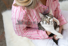 A white and tabby kitten held in a womans lap while looking at the camera