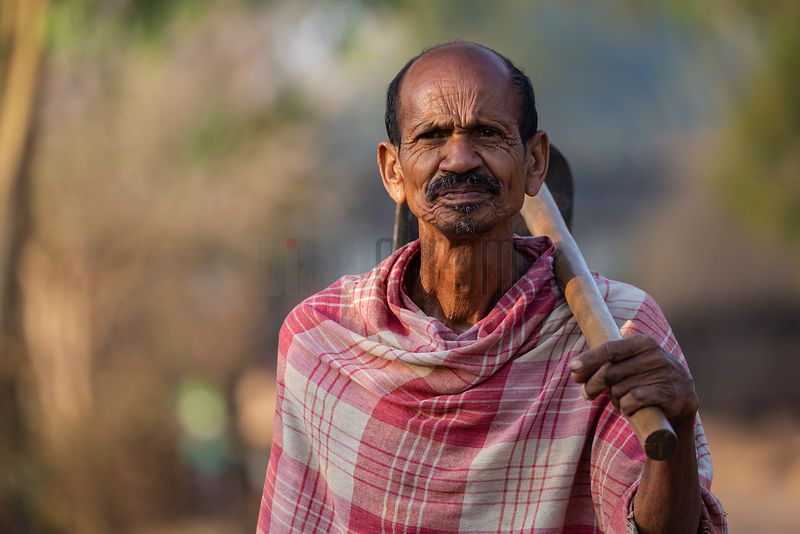 Portrait of a Man from a Rural Village Carrying a Hoe