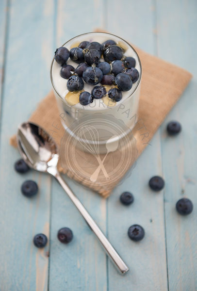 Blueberries in natural yoghurt with drizzled honey, dessert or snack. Presented in a glass tumbler.
