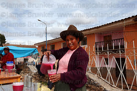 Quechua lady serving chicha made from quinoa and airampu fruit in Chinchero market , near Cusco , Peru
