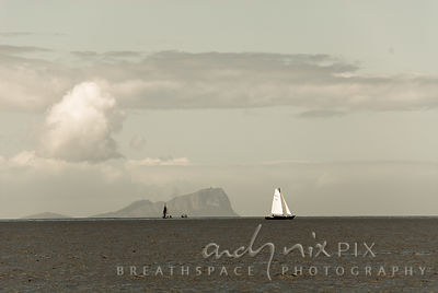 A fishing boat and two yachts sailing on False Bay with Cape Hangklip in the background, cumulus clouds.