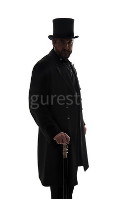 A Victorian man in a hat and coat, standing with a cane, in silhouette – shot from eye level.