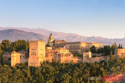 Alhambra palace with Sierra Nevada mountains at sunset, Spain