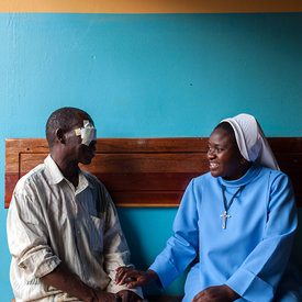 Sister Exildah talks to and comforts a cataract patient after surgery