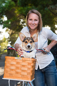 Corgi Puppy in Bicycle Basket with Young Woman Standing Behind