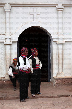 Men in traditional dress standing outside church , Taquile Island , Peru