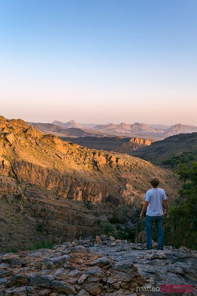 Man looking at rocky mountains at sunset, Oman
