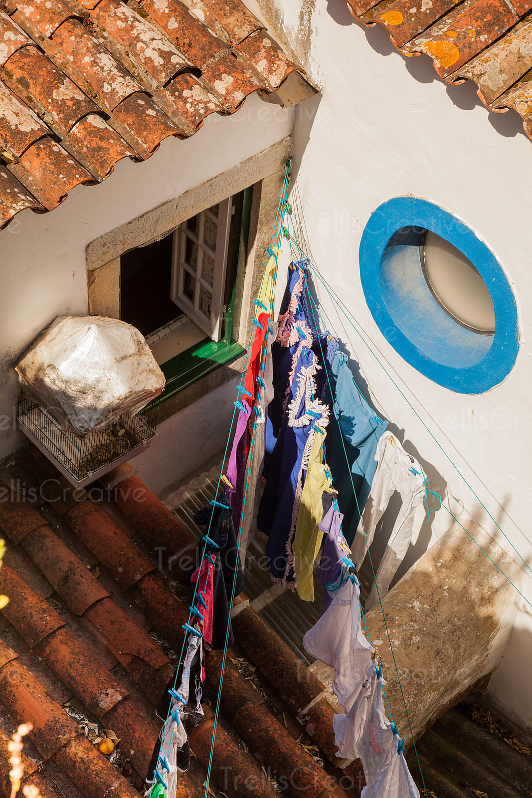 Colorful laundry hangs on a clothesline outside in the sun to dry.